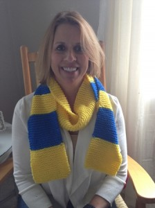 Southborough resident Carol Venie models one of the scarves she knitted for runners in the Boston Marathon. (Photo/submitted)