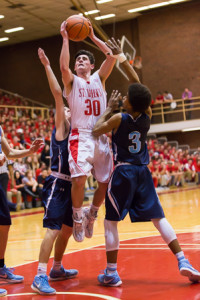 Tyler Mola goes up between two defenders as he shoots.