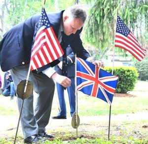 Richard Schofield places a British flag on the grave of Sgt. Alexander J. MacIsaac.