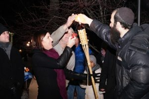 State Rep. Hannah Kane lights the first candle of the menorah.