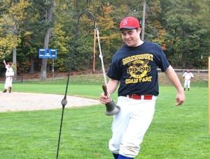Shrewsbury High School senior Will Wright rings a bell near home plate, an old-fashioned baseball rule.