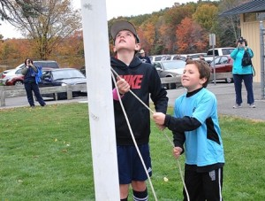 Connor Mongeon, 12, and his brother Owen, 8, raise the American flag.