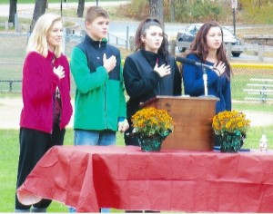 (l to r) Alexis Green, Kealan Green, Jenna Taylor, and Kelsi Taylor recite the Pledge of Allegiance. The four are great-grandchildren of Grace Dean Backholm, the niece of Charles Dean. Photo/submitted