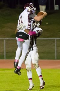 Algonquin quarterback Ryan Barry celebrates with a teammate after rushing for a touchdown in the final minutes of a game against Shrewsbury