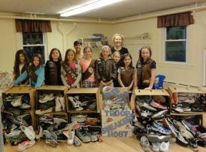 The troop proudly displays the shoes they collected.