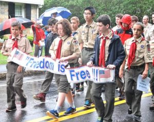 """Boy Scouts carry a banner proclaiming, """"Freedom is not free!"""" Photo/Ed Karvoski Jr."""
