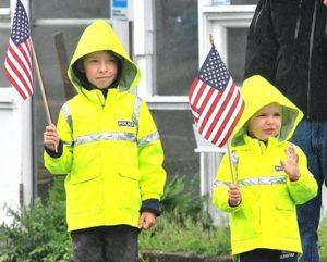 The Rice brothers – Blake, 7, and Patrick, 4, wave flags while watching the parade. Photo/Ed Karvoski Jr.