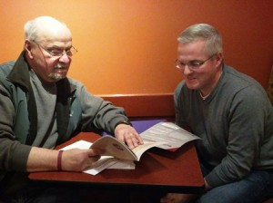 Denis Herlihy (r) and Dick Dion, co-facilitators for the Shrewsbury-based Central Massachusetts Multiple Myeloma Support Group, review informational pamphlets they provide at meetings for members. Photo/Lori Berkey