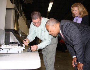 Gov. Deval Patrick is given a demonstration of the work done at Phoenix Communications.