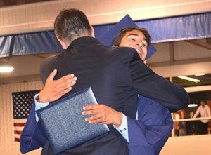 With diploma in hand, Ben George gets a congratulatory hug from Principal Todd Bazydlo. Photos/Ed Karvoski Jr.
