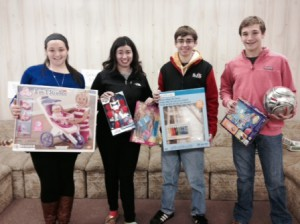 (l to r): Ali Manzello, Michaella Petrucci, Colin Buckley, and Max Kotsopoulos hold some of the presents donated to the 10th annual charity toy drive for children hosted by Shrewsbury Youth and Family Services (SYFS) and the Worcester County Department for Children and Families.  Photo/submitted