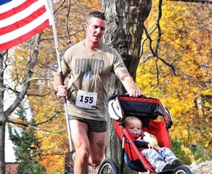 Seamus Shanley of Shrewsbury, a Marine Corps veteran and Worcester firefighter, approaches the finish line with his son Quinn, 1.