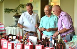(l to r) Mike Rooney, Jack Perreault and Bob Jacques take their chances at the bag raffles.
