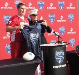 Sean Ragan receives his Semper Fidelis All-American Bowl shirt from 1st Lt. Stefan Milan, executive officer, Marine Recruiting Station, Springfield.
