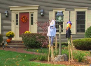 A colorful wreath of leaves along with scarecrows and pumpkins brighten this front door.