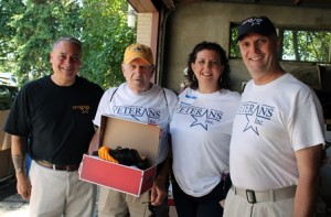 Veterans Inc. volunteers Anthony Rebello, Donald Brickman, Denise Pierce, and Dan Ward pose for a photo. Brickman holds the New Balance sneakers given free to all attending veterans.
