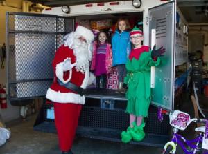 Santa with (l to r) Julianna Flores,5, Maddie Faucher, 6, and Charlie Pratt.