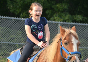 Megan, 6, enjoys taking a pony ride around the field. Photos/Ed Karvoski Jr.