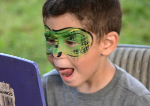 Coby Werman, 4, gets his face painted as a dinosaur. Photos/Ed Karvoski Jr.
