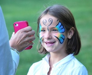 Annelise Gingrich, 7, views the photo of her painted face on her mother's cellphone.