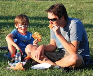 Lawson Jackson, 4, and his father Steve munch on pizza while listening to live music.