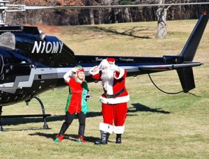 Santa's helper, aka last year's Event Chair Julia Spencer, and Santa disembark from the helicopter.