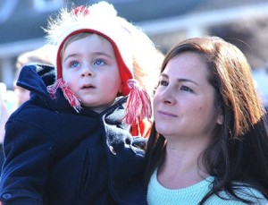 Edward Gibson, 2, and his mother Briana watch the helicopter hover over St. Mark's School field.
