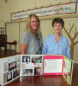 Eirinn Campaniello, current Woman's Club president, and Ginny McNamara, immediate past president, show off several of the scrapbooks that record the various club activities. (Photo/Joyce DeWallace)