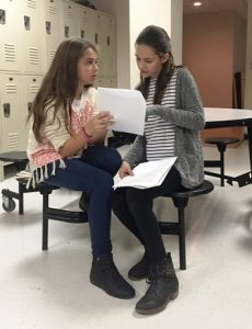 Julia Silva (l) and Megan Wagher discuss the script for the show.