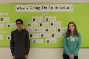 """HHS juniors and Unity Club members Clement Doucette (l) and Elizabeth Cautela stand in front of the """"What's Going on in America?"""" bulletin board in an HHS hallway. (Photo by/Dakota Antelman)"""