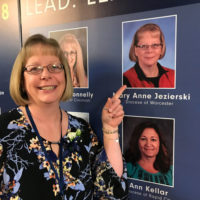 Mary Anne Jezierski stands by her photo on the board announcing the winners of the 2018 NCEA Lead, Learn, Proclaim award in Cincinnati, Ohio. Photo/submitted