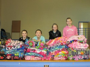 Marion E. Zeh School students admire the 39 blankets the school will be donating to Project Linus: (l to r) Lena Johnson, Gracie Sheng, Brianna Leblanc and Sophia Hjerpe.