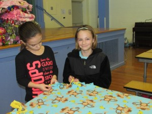 Ava DeSimone and Brianna Leblanc finish a blanket to be donated to Project Linus.
