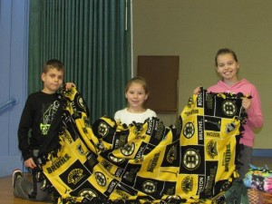 Jovani Barrett, Brianna Belanger and Sophia Hjerpe hold a Boston Bruins blanket that was made as part of Project Linus. (Photos/submitted)