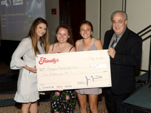 (l to r) Vanessa Larareo, girls' varsity lacrosse coach, Erin Blake and Grace Gibbons, girls' varsity lacrosse captains, and William Chiccarelli, brand communications & field marketing manager of FIC Restaurants, Inc. Photo/submitted