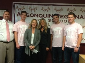 (l to r) Algonquin Regional High School Head Football Coach Justin McKay, Tim Keville, representatives of the Friends of Dana-Farber Debbie Maltzman and Marci Noeller, Jake Turner, and Mike Baker at the check presentation Oct. 10. The three students, all seniors, are wearing the t-shirts they sold during the fundraiser. (Photo/submitted)