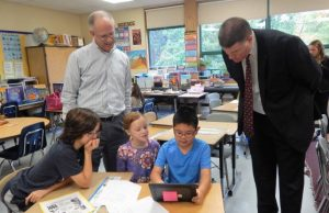 Paton School fourth-graders (l to r) Lawson Mitchell, Caroline Strickland and Owen Wang show Jim DuPont (left) and Dr. Joseph Sawyer how they use their iPads.
