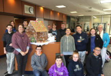 Cathy LaRoche (second from left) with members of the Shrewsbury High School M.O.V.E. program gather around Gingerbread House they created earlier this month. Photo/Melanie Petrucci