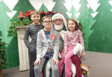 Madeline, 7, Ethan, 9 and Benjamin, 10, pose for a photo with Santa Claus at St. Mary's Annual Holly Fair Dec. 2. Photo/Melanie Petrucci
