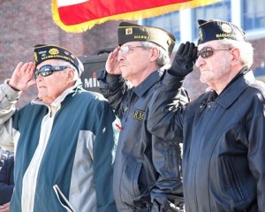 Veterans (l to r) Jack Donovan, Mike Bellows and Ron Pelletier salute as the American flag is raised.