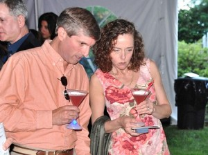 Michael Pellini and Dr. Jane Molinari check the silent auction after getting martinis served in light-up flashing glasses.
