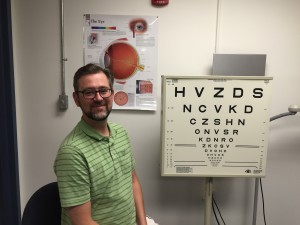 Shrewsbury resident Shaun Kinsella, director of Massachusetts Association for the Blind and Visually Impaired, sits beside the eye test chart at the agency's low vision clinic in Worcester. (Photo/Lori Berkey)
