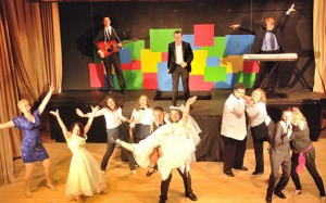"Danny Hutchins as rock-star wannabe Robbie Heart (back, center) and ""The Wedding Singer"" cast members perform ""It's Your Wedding Day."""