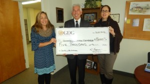 Howard Grossman presents the $5,000 donation check to Shrewsbury Education Foundation representatives. (Photo/submitted)