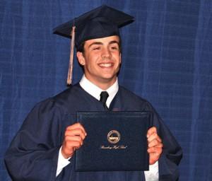 Logan Campos displays his diploma.