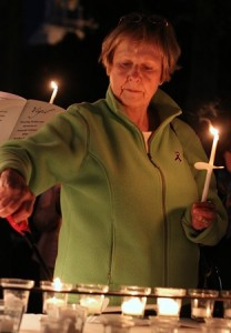 Bette Oliver lights candles to commemorate victims of domestic violence.