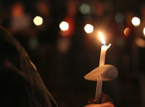 A candle is held by a participant at the domestic violence vigil.