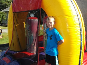 After completing the inflatable obstacle course, Dillon, 7, of Shrewsbury, poses for a photo.