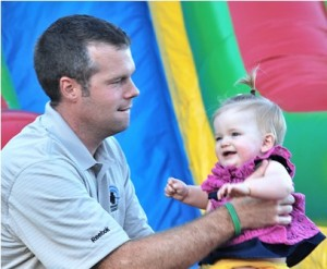 Brad Young plays with his daughter, Arden, 11 months, in the bouncy house.