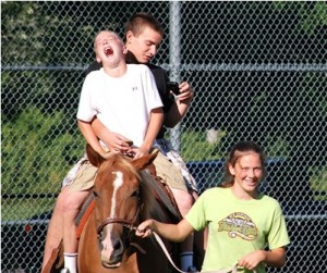 (l to r) Kyle Henderson and Isaiah Keegan, both entering eight grade at Trottier Middle School, share a laugh as they try to photograph themselves with a camera phone while riding a horse led by Delaney Smolinski of Ridge Valley Stables.